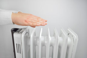 woman is warming up her hands over electric heater